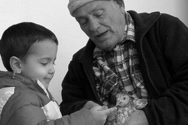 Ein Kind und ein älterer Mann betrachten ein Huhn